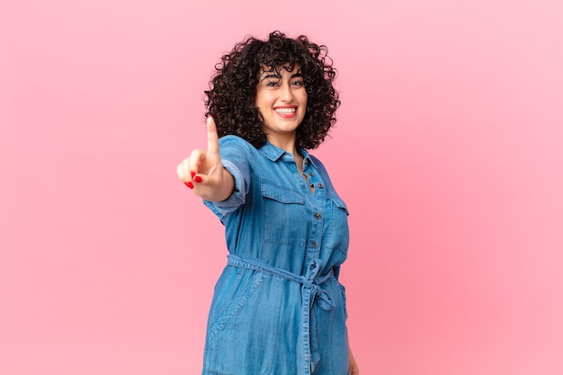 Mooie arabische vrouw die trots en zelfverzekerd glimlacht en nummer één maakt