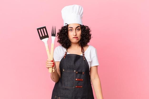 Mooie arabische vrouw die verbaasd en verward kijkt. barbecue chef-kok concept