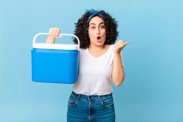 Mooie arabische vrouw die verbaasd kijkt in ongeloof en een draagbare koelkast vasthoudt