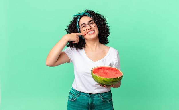 Mooie arabische vrouw die vol vertrouwen glimlacht, wijst naar haar eigen brede glimlach en een watermeloen vasthoudt. zomer concept