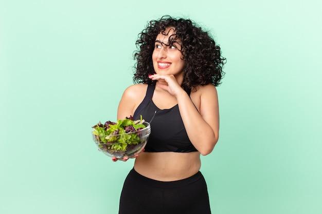 Mooie arabische vrouw die vrolijk lacht en dagdroomt of twijfelt en een salade vasthoudt. dieet concept
