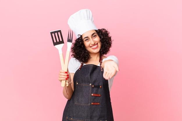 Mooie arabische vrouw die vrolijk lacht met vriendelijk en een concept aanbiedt en toont. barbecue chef-kok concept