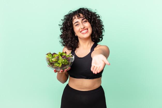 Mooie arabische vrouw die vrolijk lacht met vriendelijk en een concept aanbiedt en toont en een salade vasthoudt. dieet concept