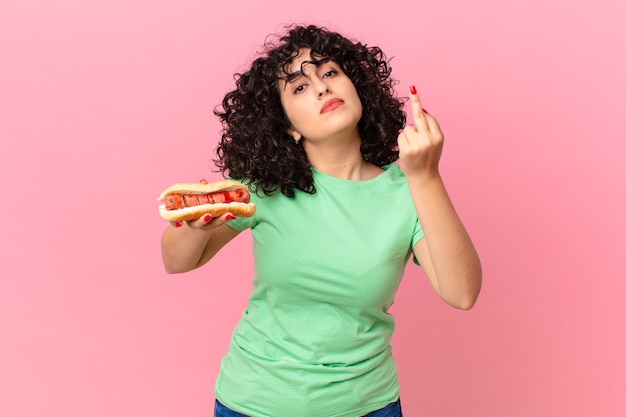 Mooie arabische vrouw die zich boos, geïrriteerd, opstandig en agressief voelt en een hotdog vasthoudt
