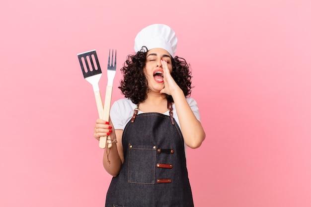 Mooie arabische vrouw die zich gelukkig voelt, een grote schreeuw geeft met de handen naast de mond. barbecue chef-kok concept