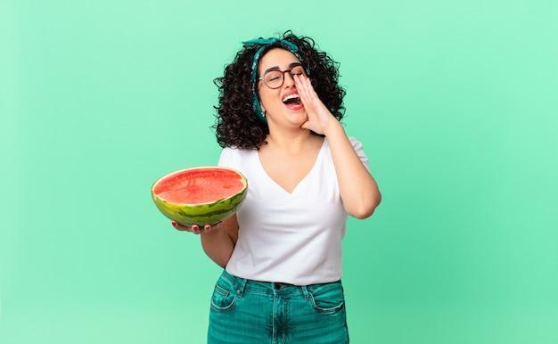 Mooie arabische vrouw die zich gelukkig voelt, een grote schreeuw geeft met de handen naast de mond en een watermeloen vasthoudt. zomer concept