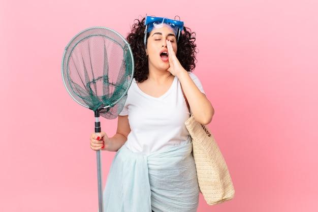 Mooie arabische vrouw die zich gelukkig voelt, een grote schreeuw geeft met de handen naast de mond met een bril. vissers concept