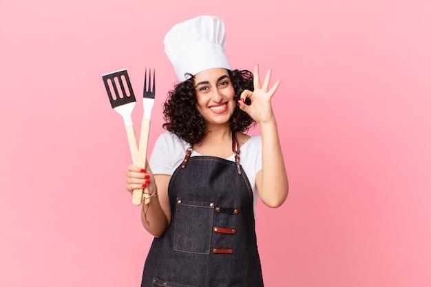 Mooie arabische vrouw die zich gelukkig voelt en goedkeuring toont met een goed gebaar. barbecue chef-kok concept