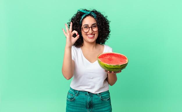 Mooie arabische vrouw die zich gelukkig voelt, goedkeuring toont met een goed gebaar en een watermeloen vasthoudt. zomer concept