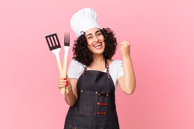 Mooie arabische vrouw die zich geschokt voelt, lacht en succes viert. barbecue chef-kok concept