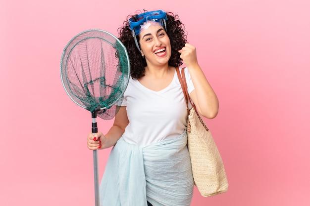 Mooie arabische vrouw die zich geschokt voelt, lacht en succes viert met een bril. vissers concept
