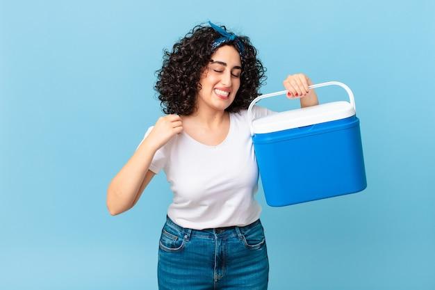 Mooie arabische vrouw die zich gestrest, angstig, moe en gefrustreerd voelt en een draagbare koelkast vasthoudt