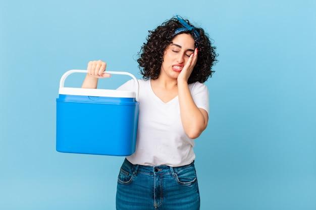 Mooie arabische vrouw die zich verveeld, gefrustreerd en slaperig voelt na een vermoeiende bezigheid en een draagbare koelkast vasthoudt