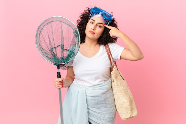 Mooie arabische vrouw die zich verward en verbaasd voelt en laat zien dat je gek bent met een bril. vissers concept