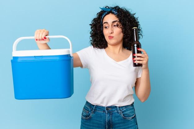 Mooie arabische vrouw met een draagbare koelkast en een biertje