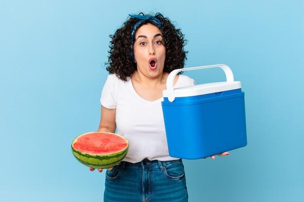 Mooie arabische vrouw met een draagbare koelkast en een watermeloen
