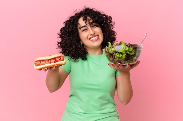 Mooie arabische vrouw met een salade en een hotdog. dieet concept