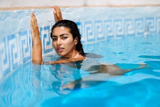 Mooie arabische vrouw ontspannen in het zwembad.