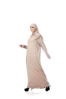 Mooie arabische vrouw poseren in stijlvolle hijab geïsoleerd op studio achtergrond mode concept