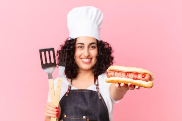 Mooie arabische vrouwenbarbecue die hotdogs voorbereidt