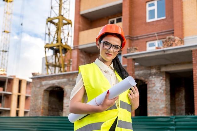 Mooie architect met blauwdrukken op rollen op de bouwplaats