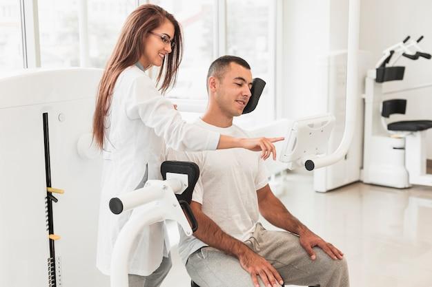 Mooie arts die patiënt toont hoe te om medisch hulpmiddel te gebruiken