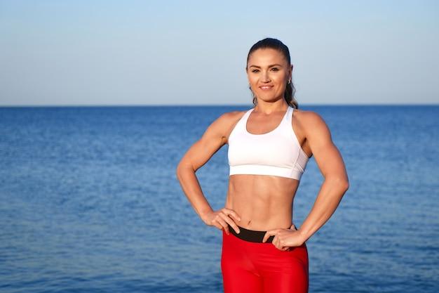 Mooie atleet vrouw in rode sportkleding poseren op de achtergrond van het landschap van de zee. ochtendtraining bij de oceaan, gezonde levensstijl