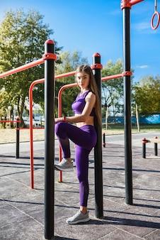 Mooie atleet vrouw ochtend oefeningen op de straat speeltuin. trainen in de open lucht. workout voor vrouwen