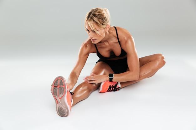 Mooie atletenvrouw die uitrekkende oefeningen doet