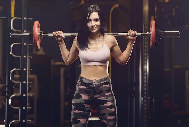 Mooie atletische jonge vrouw die in gymnastiek uitwerkt