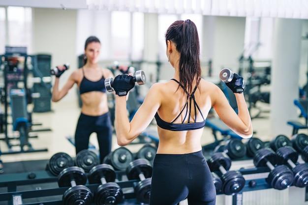 Mooie atletische jonge vrouw die oefening in de sportschool maakt. jonge vrouw met gespierd lichaam. fitness concept.