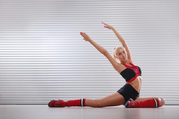 Mooie atletische jonge vrouw die zich uitstrekt voor haar training