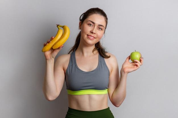 Mooie atletische jonge vrouw in sportkleding met een appel en een banaan in haar handen.