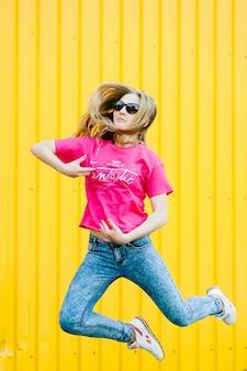 Mooie atletische jonge vrouw met lang blond haar in roze shirt, spijkerbroek. in witte sneakers. poseren, glimlachend op muur van de garage op gele muur plaats voor tekst. bril. vliegen. springt