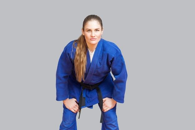 Mooie atletische karate vrouw in blauwe kimono met zwarte gordel in de strijd tegen houding kijken naar de camera. japans vechtsportenconcept. binnen, studio-opname, grijze achtergrond