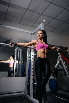 Mooie, atletische sexy meisje poseren in de sportschool na een zware training. fitness, bodybuilding.