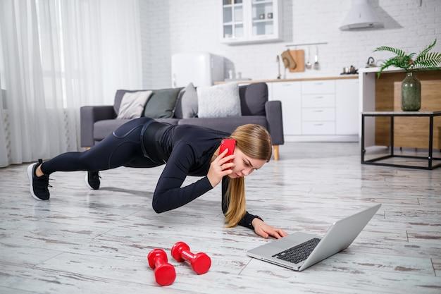 Mooie atletische vrouw in een zwarte top en legging die thuis sport en aan de telefoon praat. motivatie om te gaan sporten. gezonde levensstijl.