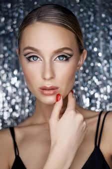 Mooie avond oogmake-up van een blonde vrouw op een glanzende achtergrond. close-upportret van een vrouw, perfecte oogmake-up, huidzorg