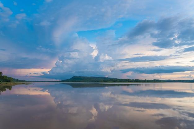 Mooie avondluchtwolken bij zonsondergang op het kalme meer.