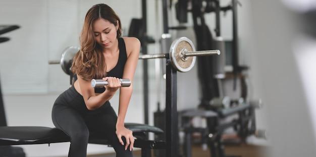 Mooie aziatische atletische vrouwen opheffende domoor in de gymnastiek van de gewichtsgeschiktheid