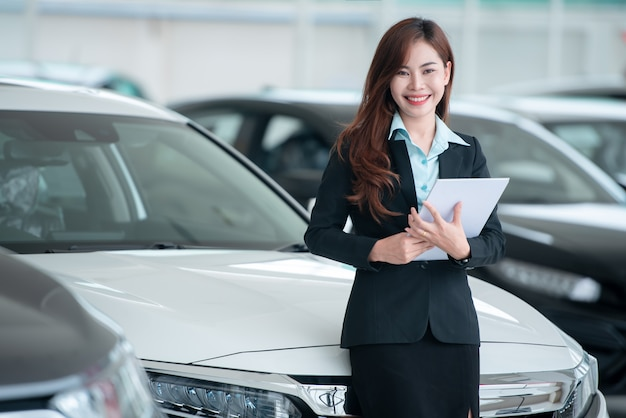 Mooie aziatische autodealers verkopen graag nieuwe auto's in de showroom en verkopen graag auto's.