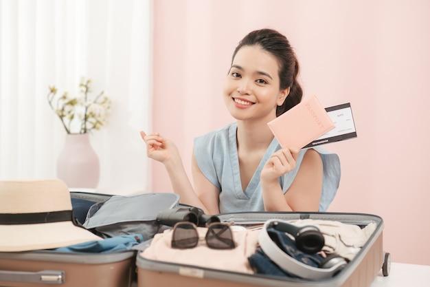Mooie aziatische bedrijfsvrouw die bedrijfpaspoort en kaartje met gele koffer glimlachen om het reizen voor reistoerist op vakantieweekend voor te bereiden.