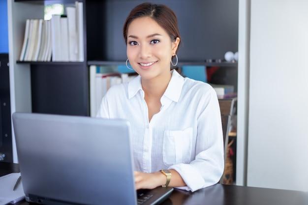 Mooie aziatische bedrijfsvrouwen die document controleren en notitieboekje voor thuis het werken gebruiken