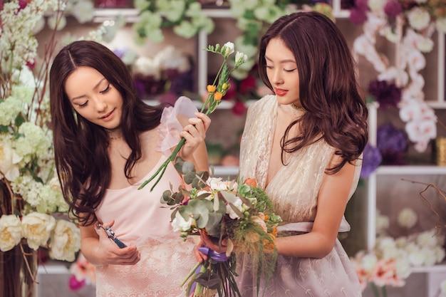 Mooie aziatische bloemistmeisjes die boeket bloemen te koop tegen bloemenbokeh maken