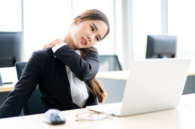 Mooie aziatische bureauvrouw die een probleem van het bureausyndroom heeft