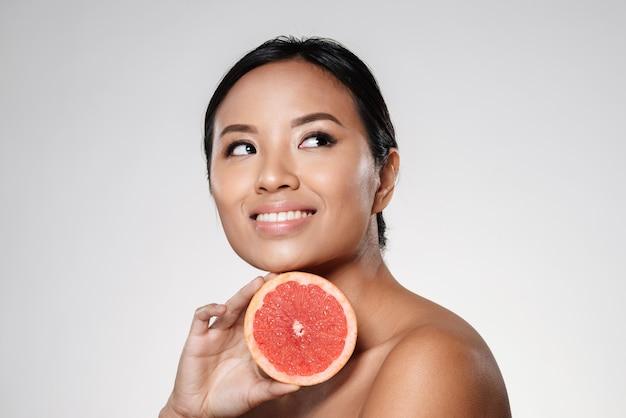 Mooie aziatische dame die opzij kijkt en grapefruitplak dichtbij gezicht houdt