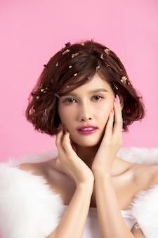 Mooie aziatische die vrouw op roze wordt geïsoleerd