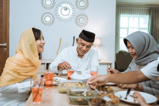 Mooie aziatische familie die thuis van hun iftardiner geniet. ramadan kareem islam breekt vastentraditie Premium Foto