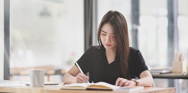 Mooie aziatische freelancer die haar idee in notitieboekje schrijft