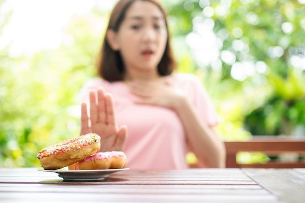 Mooie aziatische gezonde vrouw van middelbare leeftijd zitten en weigeren om snoep te eten
